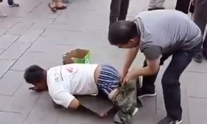 Man takes off beggar's pants in China and reveals...
