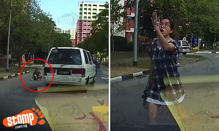 Woman sits on road along Tampines St 72 , then blocks vehicles and yells at drivers