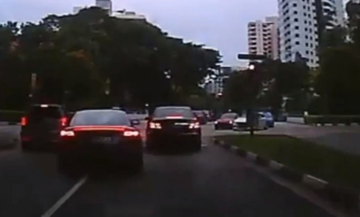 Audi driver squeezes in between two cars to move off -- while lights are still red