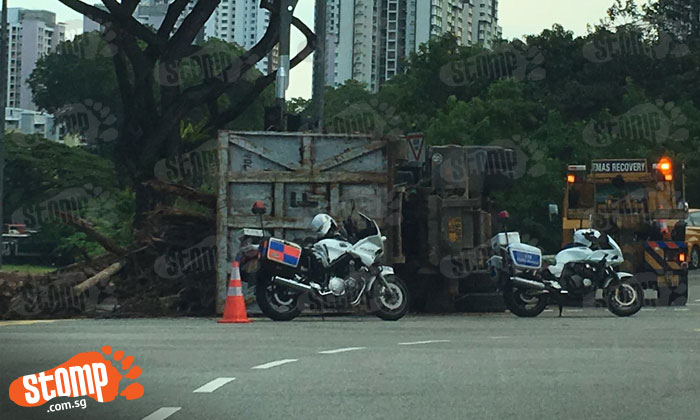 What happened? Tipper truck carrying branches and logs topples on its side at Jurong Town Hall Rd