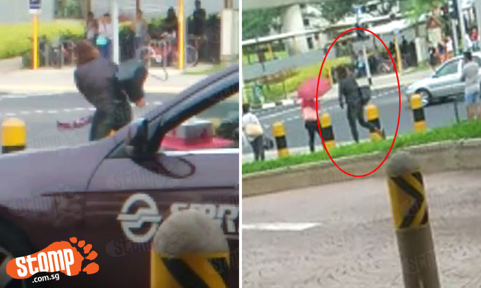 Woman walks on road and shouts car plate numbers as vehicles whizz by outside Tampines Mall