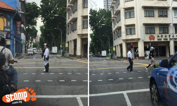 Two uncles spotted taking photos in the middle of the road when red man is flashing
