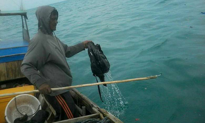 A fisherman nets a bag belonging to passengers of a police plane that crashed on Dec. 3 in the ocean between Mensanak Island and Gentar Island in Riau Islands. PHOTO: JAKARTA POST/ ASIA NEWS NETWORK