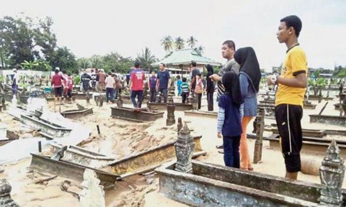 Nature's fury: Residents looking at the graveyard in disbelief after swift currents wreaked havoc and four recently buried bodies were found floating nearby. Photo: The Star/Asia News Network