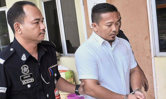 Mohd Ezlie being escorted by police officers at the Sessions Court in Selayang. Photo: Bernama via The Star