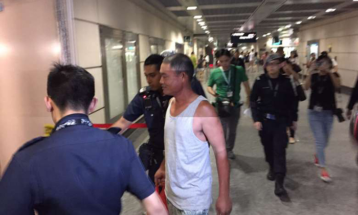 A man being led away by the police into the staff area at Hougang MRT station.ST PHOTO: NEO XIAOBIN
