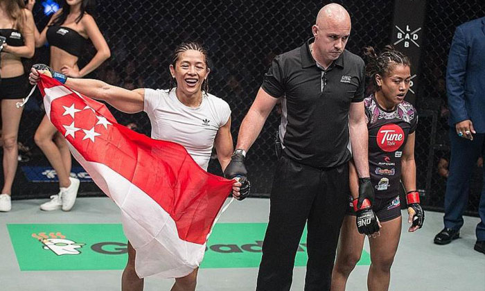 May Ooi holding the Singapore flag after beating Malaysia's Ann Osman on her ONE Championship debut in Kuala Lumpur.PHOTO: ONE CHAMPIONSHIP