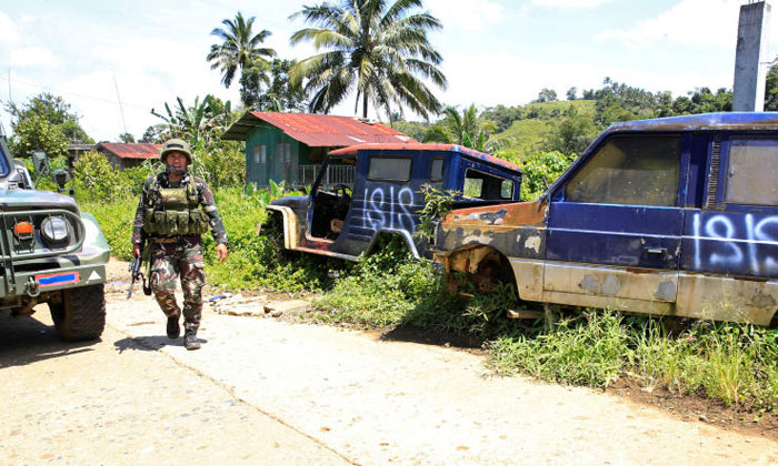 A government soldier patrols a deserted mountain village after pro-Islamic State militants, who had earlier taken over the village, had left, on the outskirts of Marawi city. Photo: Reuters