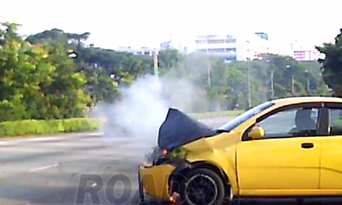 The front part of the car was on fire and smoke can be seen coming out of the bonnet of the car. PHOTO: ROADS.SG (FACEBOOK)