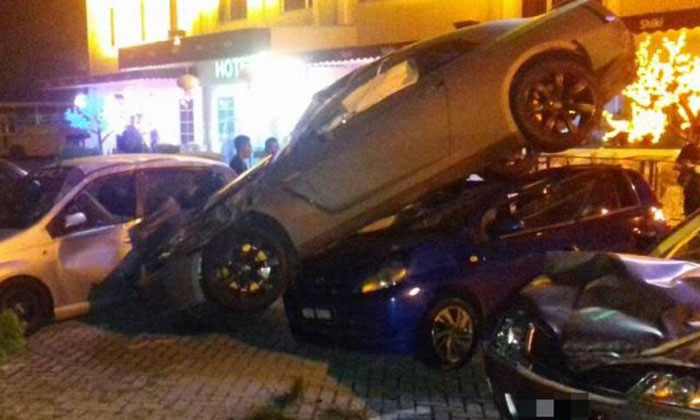 The impact was so great that the black Nissan GTR driven by the 44-year-old was wedged between two Perodua Viva. Photo: The Star