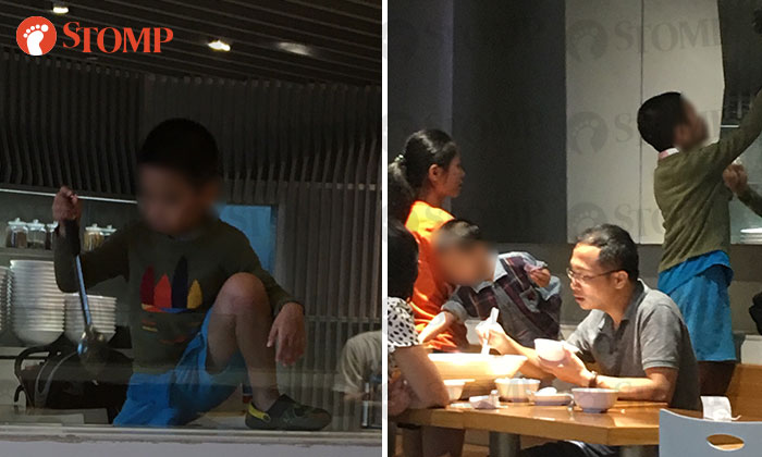 The unruly boy climbing over a counter and playing with a ladle (left) while his family (right) continued eating.