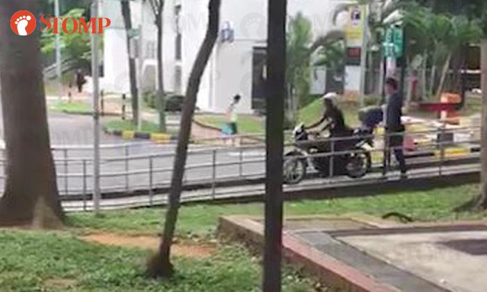 A motorcyclist can be seen riding down a walkway while a pedestrian had to lean on the railing to allow him to pass