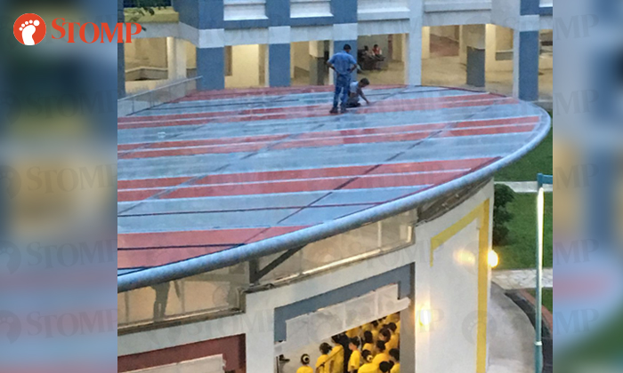 Stomper Rafcame across three men walking on the rooftop of a multi-purpose hall at Woodlands Drive 16.