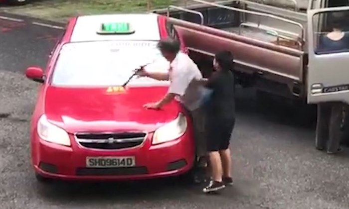 An elderly man was caught on video hitting a taxi while a little boy restrains him
