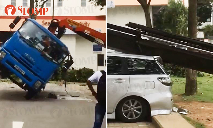 A truck tipped over (left) at a carpark in Geylang Lorong 25, causing a car to be damaged by its hydrualic arm. (right)