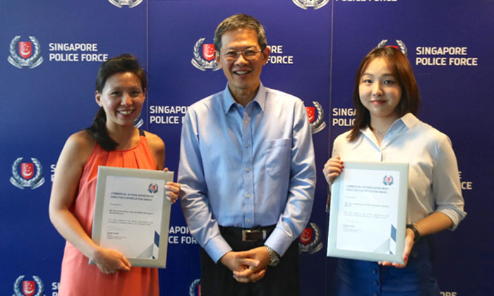 Director CAD Mr. David Chew with OCBC staff, Ms Seah Hoon Hoon June (left) and Ms Yao Liang Bing (right). Photos: Singapore Police Force