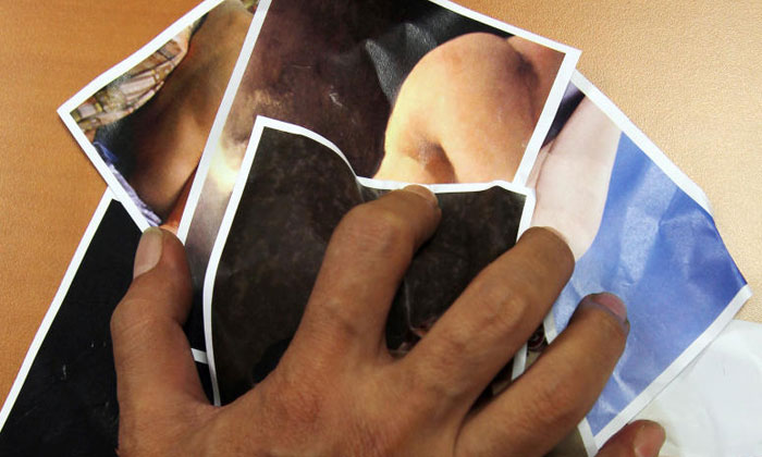 Posedphoto of a man holding obscene photos. PHOTO: TNP