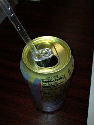 That little tab around the top of soda cans was designed to hold your straw. Simply twist the tab around, and center your straw and you're done.