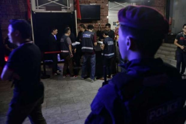 Police checking a club's security officers' passes and whether its staff are registered in the wee hours of Saturday (March 18). ST PHOTO: KEVIN LIM