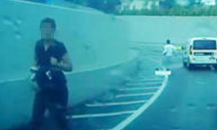 The female passenger (in black) was forced to alight the vehicle by the driver (in white) Photo: Shin Min Daily News