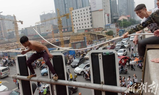 Onlookers try to help man perched on top of traffic light in China -- but make everything worse