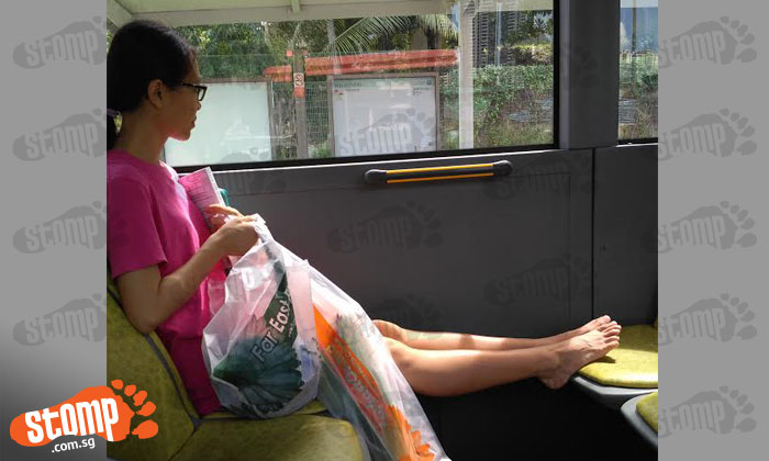 Inconsiderate passenger airs her feet on bus seat