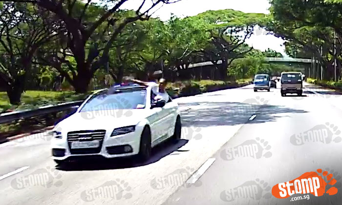 Audi driver speeds on PIE while passenger sticks body out of car and gestures at other drivers
