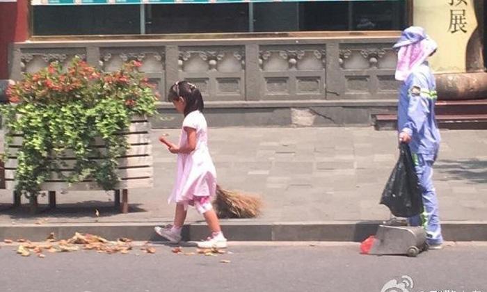 Little girl helps street cleaner mum sweep Shanghai streets under sweltering heat