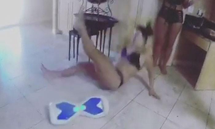 Woman in bikini falls as she tries to use hoverboard