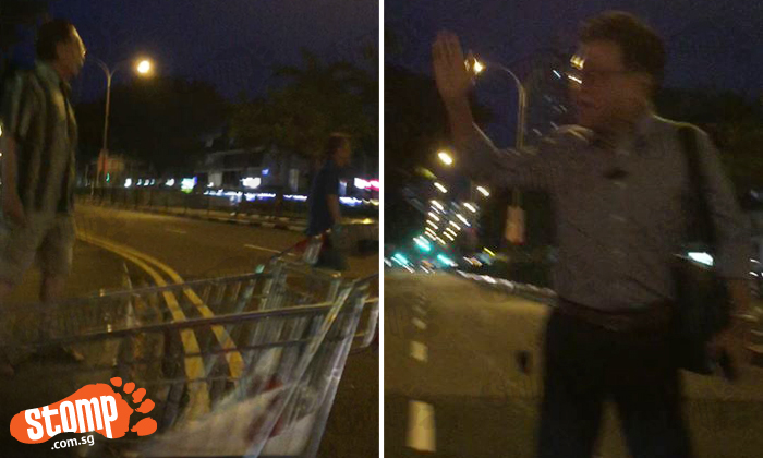 Men shout at each other in the middle of Toa Payoh road -- over a supermarket trolley