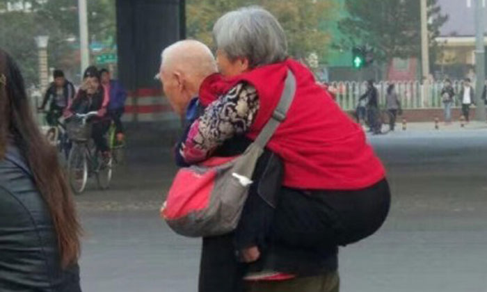 Netizens hearts melt after photos of elderly man giving his wife piggyback ride across road in China go viral