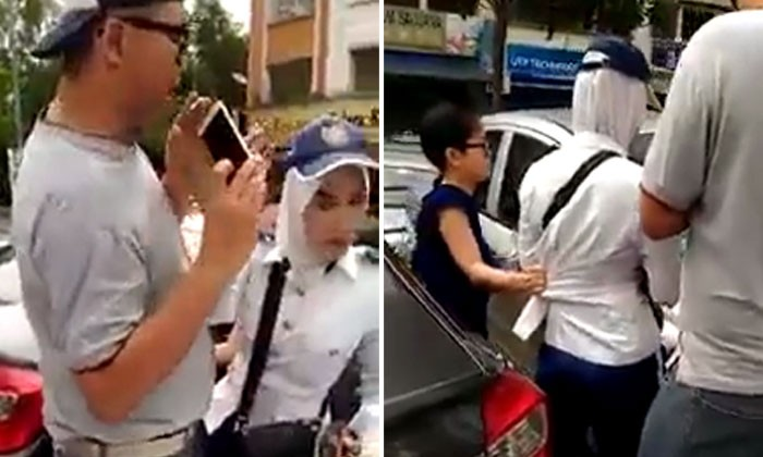Car owners refuse to let go of parking attendant in Malaysia after claiming she hurt woman's arm