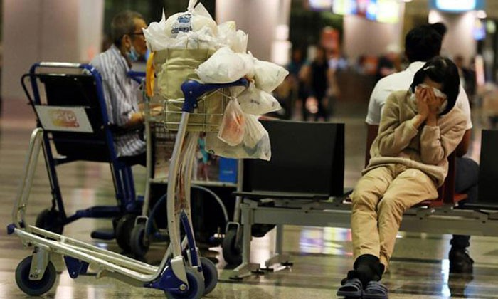 Woman sleeping in airport (Photo by Rao Jinli, Lianhe Wanbao)