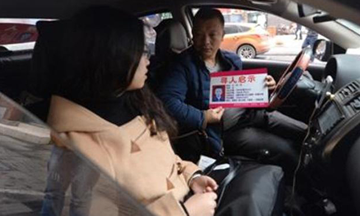 Wang Qingming shows a passenger the card with details about his missing daughter.