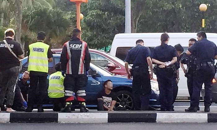 The arrested man, who allegedly wielded an electroshock weapon, is seen sitting on the road flanked by police and SCDF officers. Police investigations are ongoing in the case, the latest in a spate of incidents involving drivers of rental cars.PHOTO: SHIN MIN DAILY NEWS READER