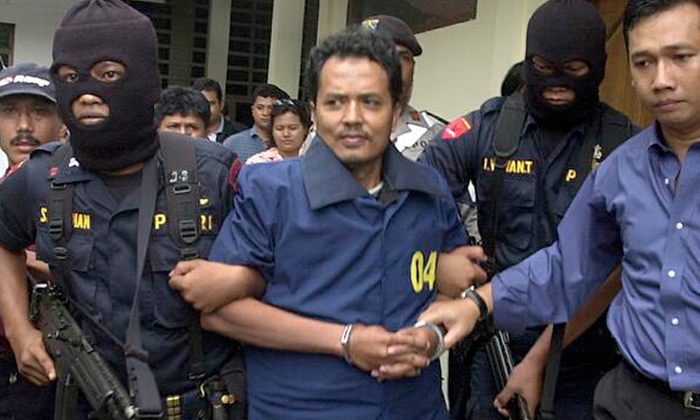 Mas Selamat Kastari (centre) leaving the Tanjung Pinang police station under heavy guard in 2003.PHOTO: ST FILE