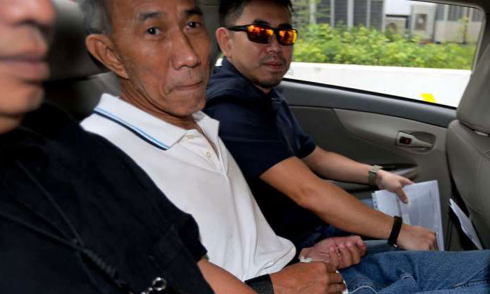 Yeo Liang Chai (centre) was charged in court with committing mischief by fire. ST PHOTOS: WONG KWAI CHOW
