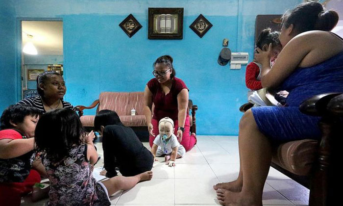 Miss Nurul Asyiqin Buang (centre) and her family in their two-room rental flat. TNP PHOTO: PHYLLICIA WANG
