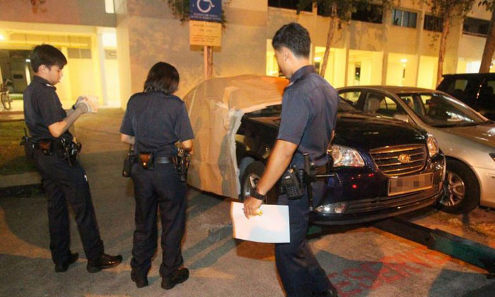 Police officers at the crime scene where money- changing business manager Ali Yousof Saiboo was robbed of more than $600,000 in cash at the carpark at Block 110 Aljunied Crescent on Nov 5, 2014. PHOTO: SHIN MIN DAILY NEWS