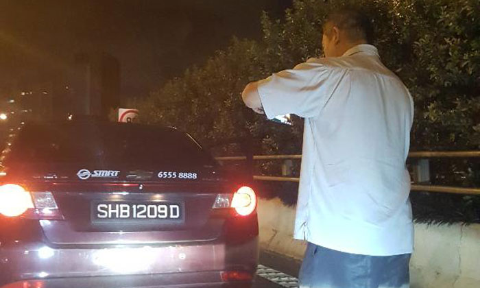The cabby taking photos of his taxi during the incident. PHOTOS: Roseline Fong