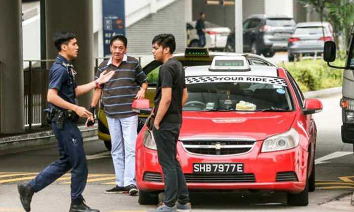 An officer attempting to mediate the argument between Mr Wu (center) and the motorist (rightmost).