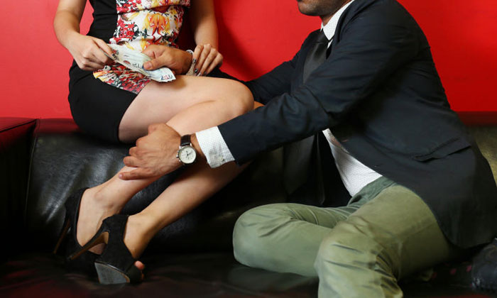 Posed photo of a woman and a man sitting on a couch as money exchange hands. PHOTO: TNP