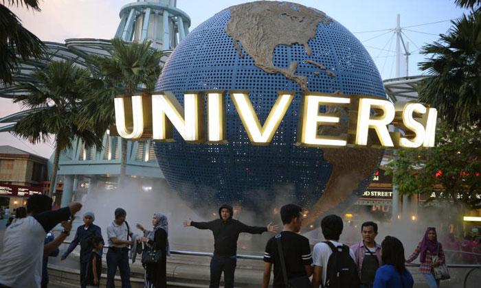 Tourists taking photos outside Universal Studios Singapore (USS). ST FILE PHOTO