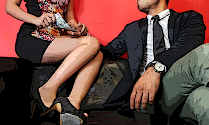 Posed photo of a woman and a man sitting on a couch as money exchange hands: TNP