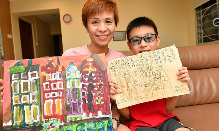 Mrs Tay and Jarret posing for a photo with some of his masterpieces.