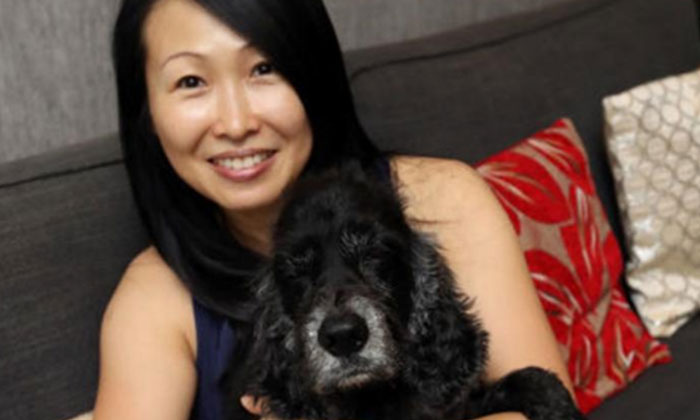 Ms Huang posing with beloved pooch. PHOTO: LIANHE WANBAO