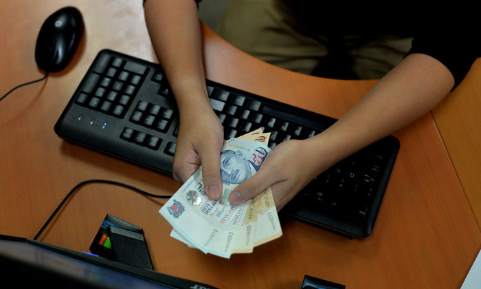 Posed photo of a person handing a wad of cash, to illustrate cheating. PHOTO: TNP