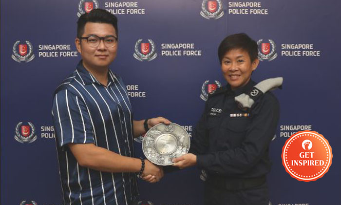 Mr Goh Tong En being awarded the Public Spiritedness Award by Deputy Assistant Commissioner (DAC) of Police Evon Ng. Photos: SPF
