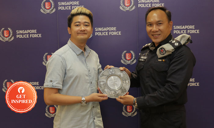 Mr Wong Dong Hai receiving the Public Spiritedness Award from Head Operations, TransCom, SUPT Alan Wong (Photo: Singapore Police Force)