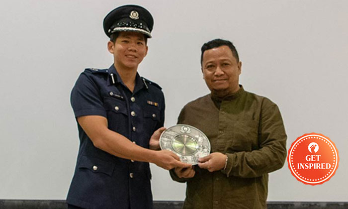 Deputy Assistant Commissioner of Police Gregory Tan, Commander of Central Police Division presenting the award to Mr Mohamad Anazri Bin Awang. PHOTO: SINGAPORE POLICE FORCE